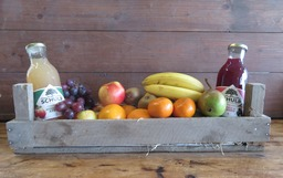 Kistje met vers fruit en grote flessen sap